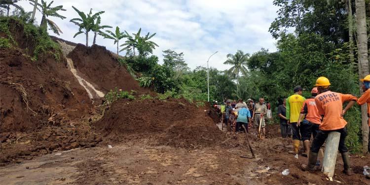 Petugas BPBD Kabupaten Blitar bersama warga membersihkan bekas-bekas timbunan tanah longsor di Desa Ngrendeng, Kecamatan Selorejo Kabupaten Blitar